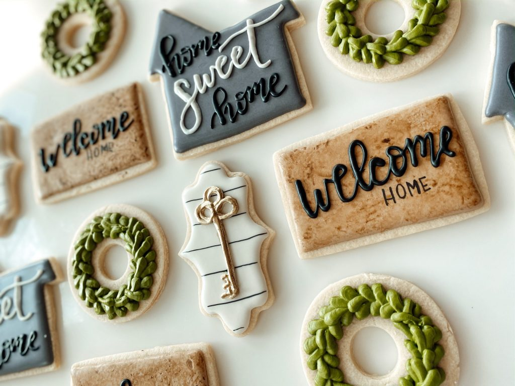 Farmhouse Style Housewarming sugar cookie set with a welcome mat cookie, a wreath cookie, a shiplap key cookie and a grey house cookie