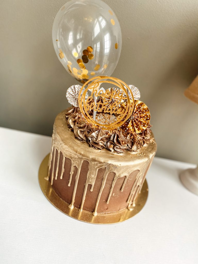 Chocolate cake with gold drip and balloons on top