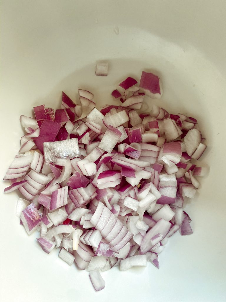 Red onion for fiesta dip in a large mixing bowl