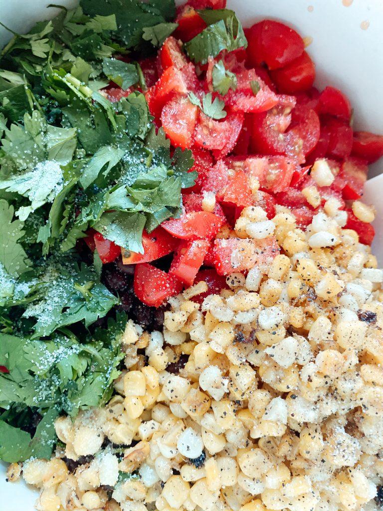 Pepper and salt on corn, tomato and cilantro